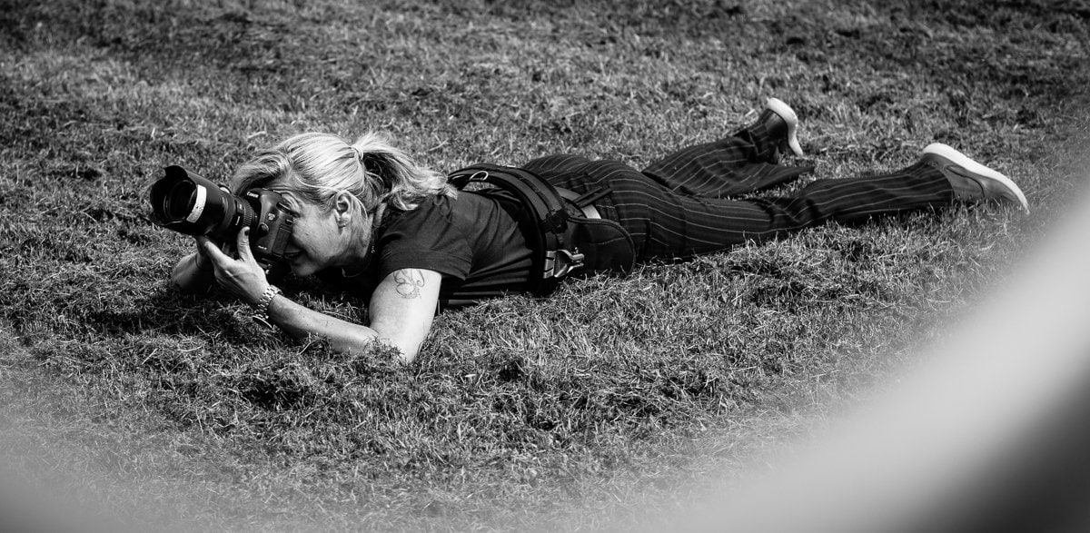 female photographer working lying on the grass black-white image