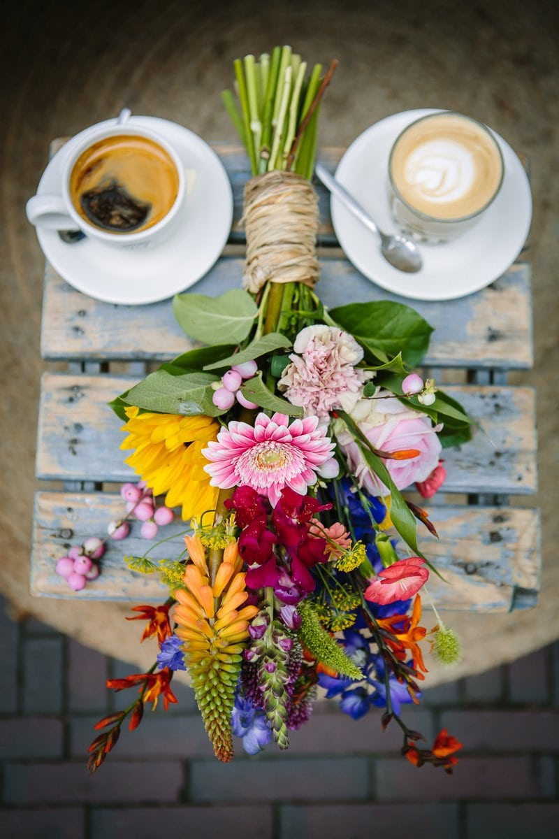 personal branding photo close-up image colourful flowers with coffee outdoor on rustic wooden table colour image natural light brand product photography